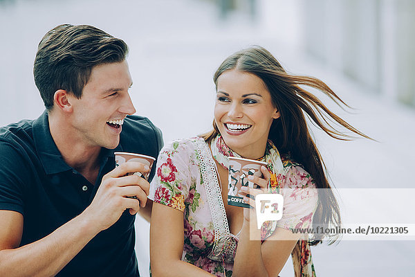 Happy young couple drinking coffee outdoors