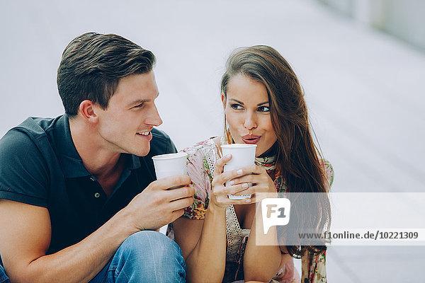 Lächelndes junges Paar trinkt Kaffee im Freien