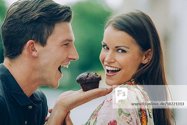 Glückliches junges Paar mit Schokoladenmuffin im Freien