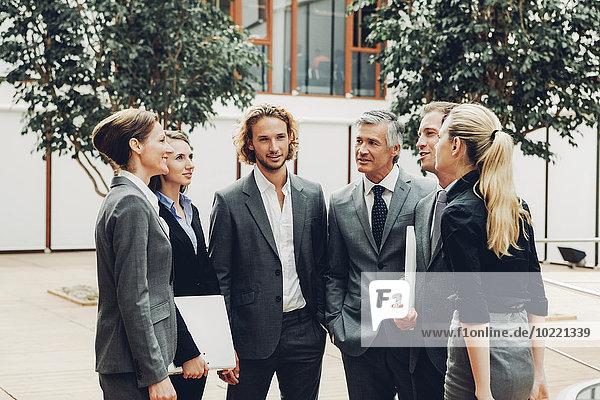 Gruppe von Führungskräften  die eine Besprechung außerhalb ihres Büros haben