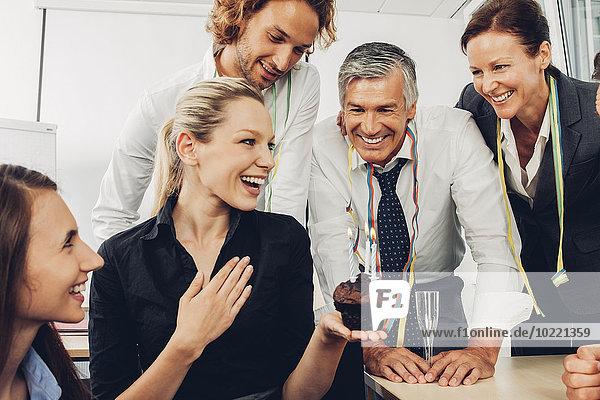 Lächelnde Führungskraft feiert Geburtstag im Büro mit Kollegen