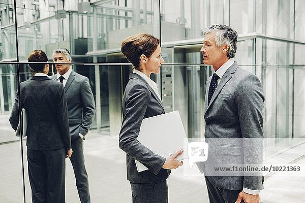 Zwei Geschäftspartner im Gespräch in einem Bürogebäudekorridor