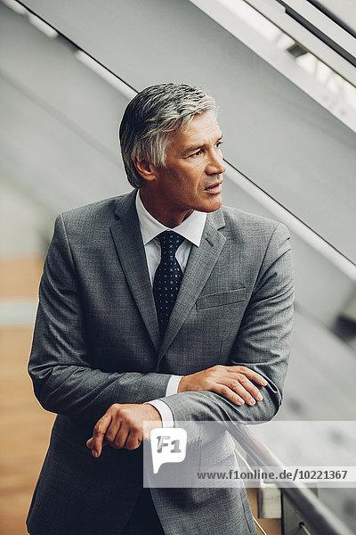 Der reife Geschäftsmann steht am Geländer und schaut weg.
