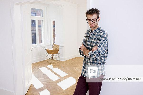 Nachdenklicher junger Mann im neuen Zuhause mit Kinderwagen im Hintergrund