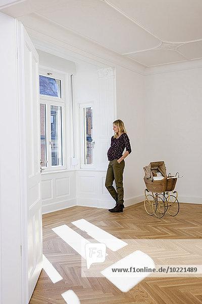 Junge schwangere Frau mit Kinderwagen in einem leeren Raum mit Blick aus dem Fenster