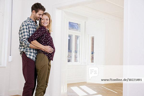 Junger Mann umarmt schwangere Frau in neuem Zuhause