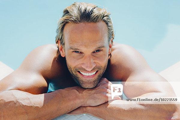 Porträt eines lächelnden Mannes im Schwimmbad  der sich an den Beckenrand lehnt.