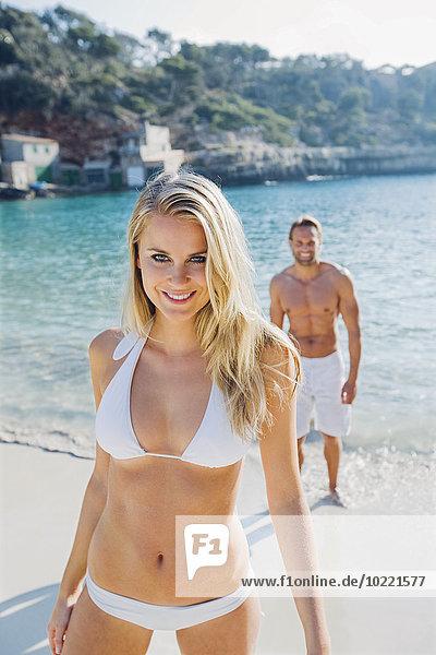 Spanien  Mallorca  lächelnde Frau im Bikini am Strand mit Mann im Hintergrund