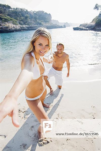 Spanien  Mallorca  Frau zieht Männerhand am Strand