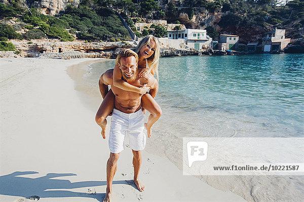 Spanien  Mallorca  Mann huckepack mit seiner Freundin am Meer