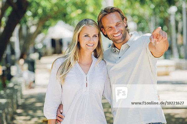 Lächelndes Paar im Freien mit einem Mann  der mit dem Finger auf sie zeigt.