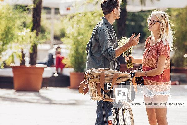 Junges Paar mit Fahrrad auf der Straße