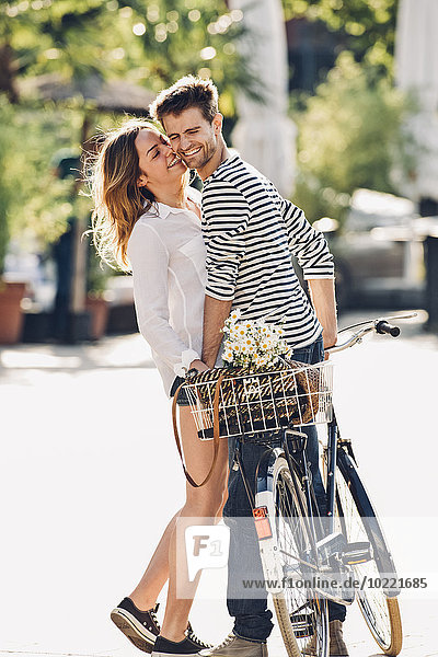 Young lovers with bicycle standing on the street