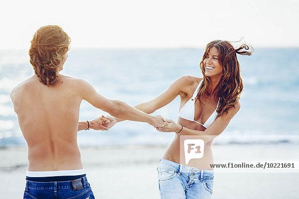 USA  Miami  glückliches junges Paar  das Spaß am Strand hat