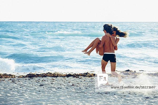 USA  Miami  junger Mann  der seine Freundin trägt und ins Meer rennt