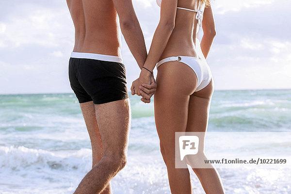 USA  Miami  junges Paar hält sich an den Händen vor dem Meer