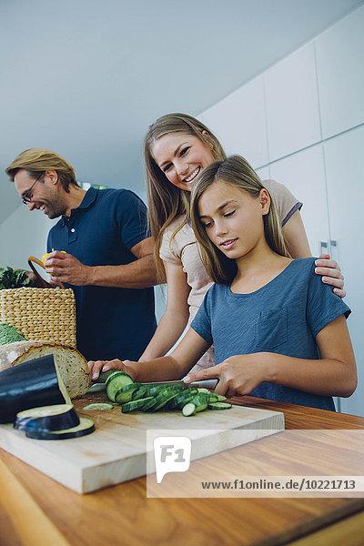 Mutter und Tochter in der Küche schneiden Gurke mit Vater im Hintergrund