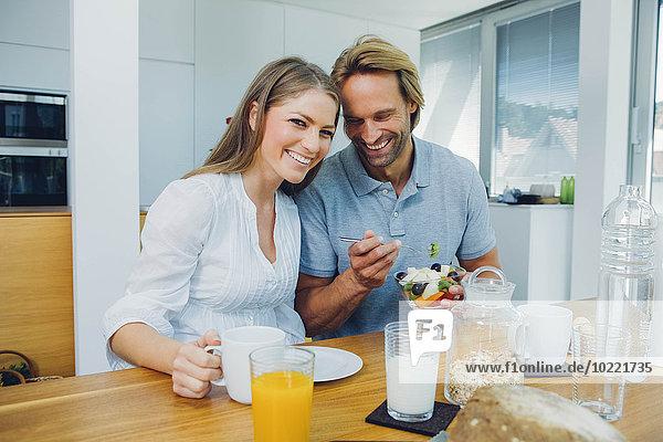 Glückliches Paar beim Essen am Küchentisch