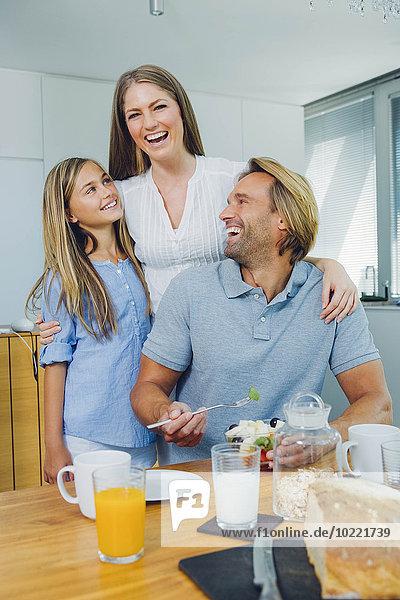 Glückliche Mutter  Vater und Tochter am Küchentisch