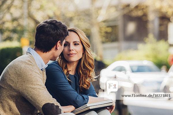 Paar im Freien mit einem Buch  das sich gegenseitig ansieht.