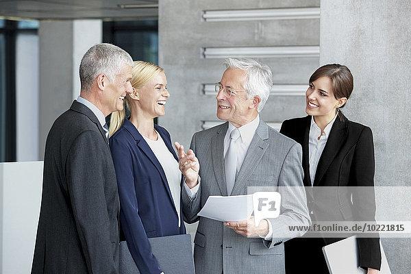 Glückliche Geschäftskollegen diskutieren über Dokumentenbüro-Lobby