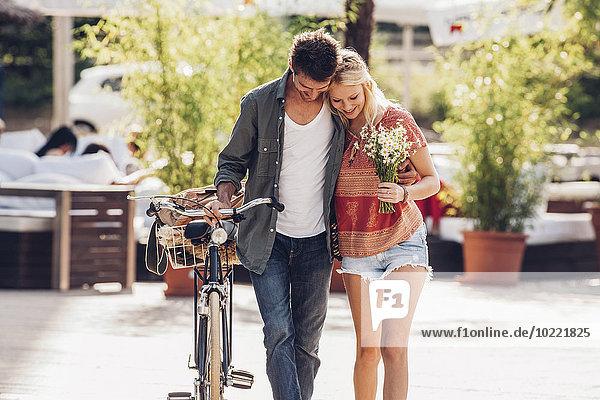 Junges Paar verliebt in Fahrrad und Blumenstrauß