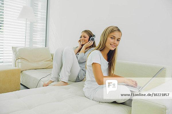 Mutter und Tochter auf Couch mit Laptop und Kopfhörer