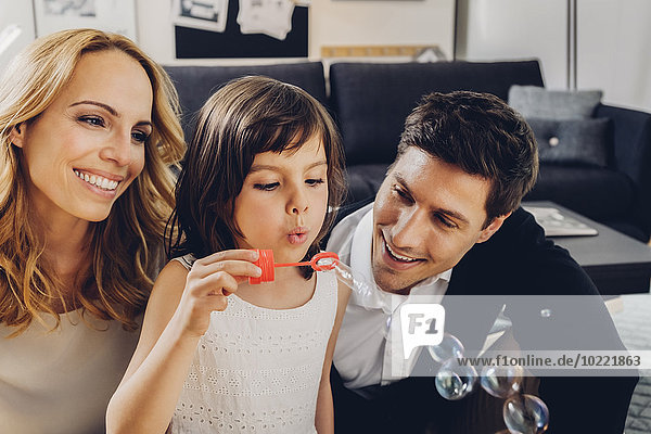 Happy family at home with girl blowing soap bubbles