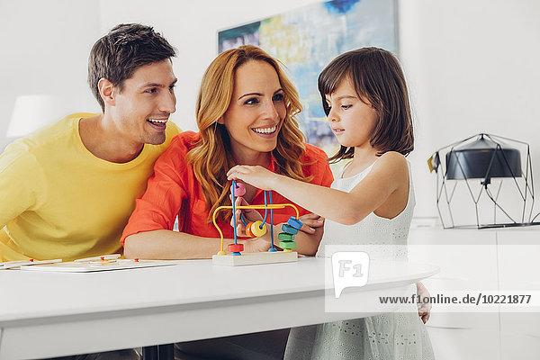 Eltern mit Tochter spielen mit Spielzeug auf dem Tisch zu Hause