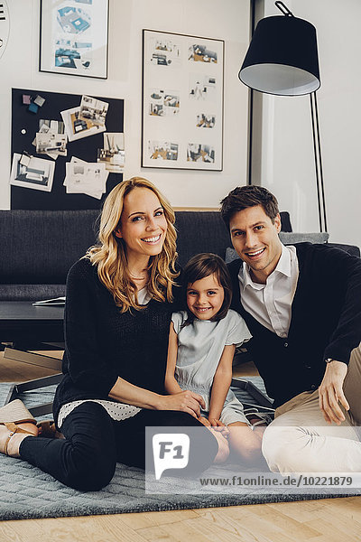 Glückliche Familie mit Tochter auf dem Boden im Wohnzimmer sitzend