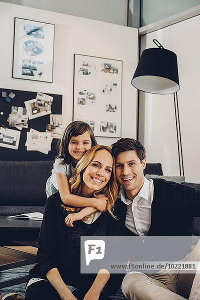 Glückliche Familie mit Tochter im Wohnzimmer