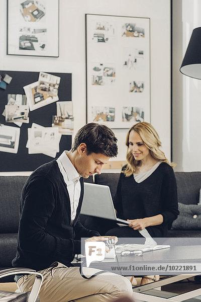 Mann und Frau im Wohnzimmer mit Kamera und Laptop