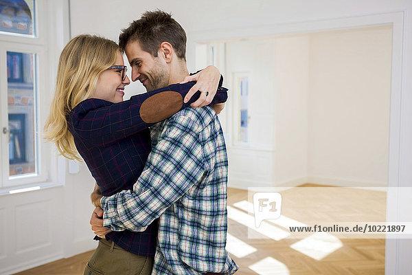 Glückliches junges Paar  das sich in einer leeren Wohnung umarmt.