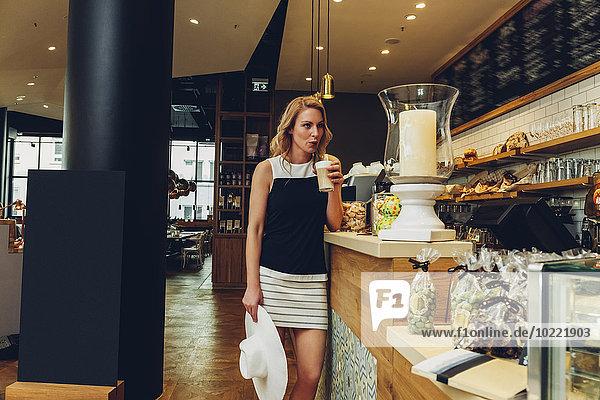 Blonde Frau steht an der Theke in einem Café und trinkt Latte Macchiato.