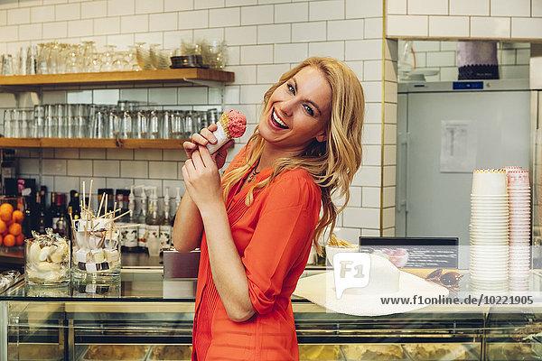 Porträt einer lachenden blonden Frau am Tresen in einer Eisdiele mit Eistüte