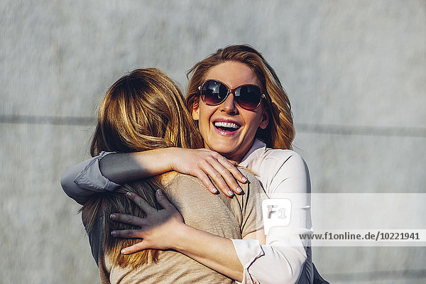 Portrait of laughing woman with sunglasses hugging her friend