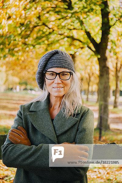 Porträt einer lächelnden Frau mit gekreuzten Armen mit Wollmütze und Handschuhen