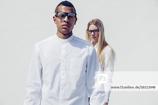 Porträt eines stilvollen jungen Paares in passender Kleidung vor weißem Hintergrund