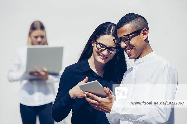 Stylish young couple wearing glasses looking together at mini tablet