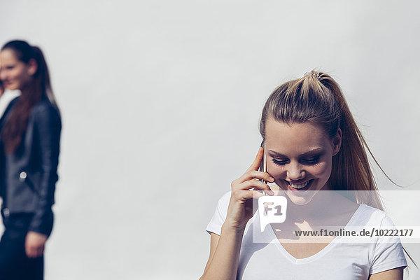 Porträt einer lächelnden jungen Frau beim Telefonieren mit Smartphone vor weißem Hintergrund