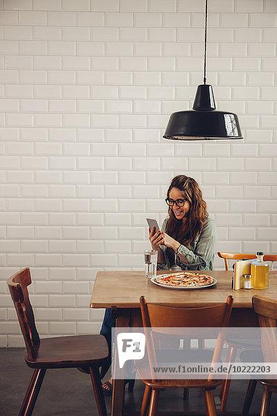 Junge Frau beim Pizzaessen im Restaurant  mit dem Handy