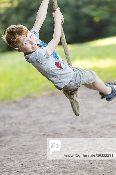 Portrait of little boy swinging with rope in a park