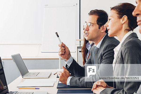 Business people sitting in office listening to presentation