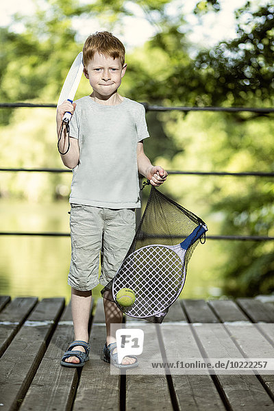 Portrait of little boy holding tennis racket and a bag