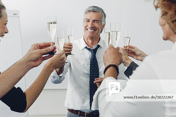 Gruppe von Geschäftsleuten  die im Büro einen Toast mit Champagner ausbringen.