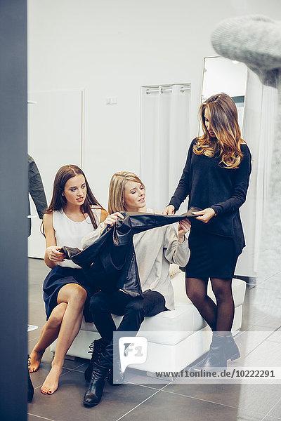 Zwei junge Frauen mit Verkäuferin in einer Boutique