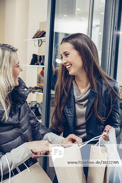 Zwei glückliche junge Frauen verlassen die Boutique mit Einkaufstaschen.