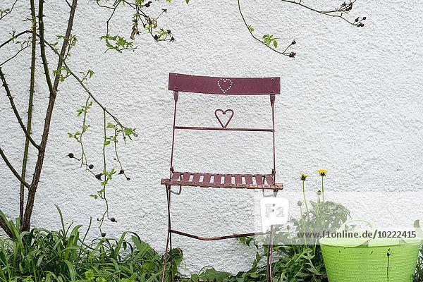 Gartenstuhl vor einer Wand