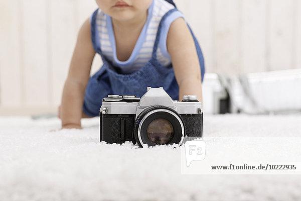 Kamera liegt auf dem Teppich  während das kleine Mädchen im Hintergrund krabbelt.