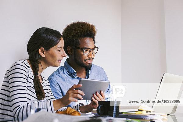 Junger Mann und Frau arbeiten mit Laptop und digitalem Tablett im Home Office